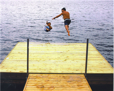 people jumping off dock into water