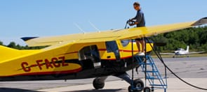 Airport worker fueling small yellow airplane